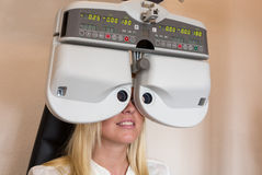 Customer of a optometrist or optician looking through phoropter Stock Image