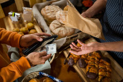 Customer paying bill by cash at bread counter Royalty Free Stock Photo