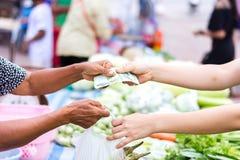 Customer paying bill by cash at market. Customer paying bill by cash at open air market Royalty Free Stock Photo