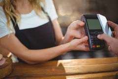 Customer paying bill through smartphone using NFC technology. In caf Royalty Free Stock Image