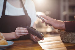 Customer paying bill through smartphone using NFC technology. In cafe Royalty Free Stock Photo