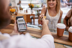 Customer paying at a cafe with credit card Stock Photos