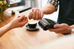 Customer Paying With Credit Card In Coffee Shop Closeup. High Resolution stock images