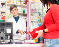 Customer paying with credit card in pharmacy Royalty Free Stock Photos