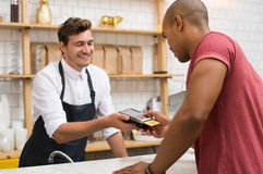 Customer paying with credit card. Waiter holding credit card swipe machine while customer typing code. African young men making payment in cafeteria with credit Royalty Free Stock Photo