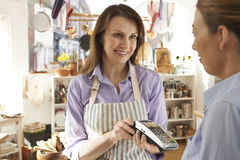 Customer Paying In Kitchen Shop Using Credit Card Terminal Royalty Free Stock Photos