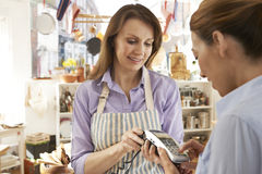 Customer Paying In Kitchen Shop Using Credit Card Terminal Stock Images