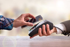 Customer paying a merchant with mobile phone front Stock Photography