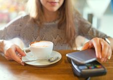 Customer Paying Through Mobile Phone. In Cafe Royalty Free Stock Photography
