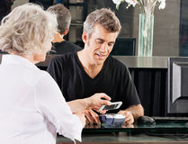 Customer Paying Through Mobile Phone At Salon Stock Image