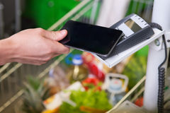 Customer paying with NFC technology. In grosery store Royalty Free Stock Photography