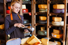 Customer paying for order of cheese in grocery shop. Stock Photos
