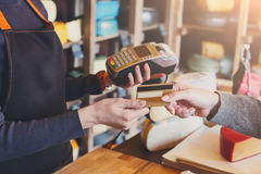 Customer paying for order of cheese in grocery shop. Stock Images