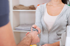 Customer paying in the shop. Customer paying with cash in the apparel shop Royalty Free Stock Images