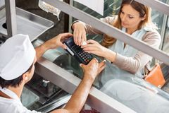 Customer Paying Through Smartphone At Butcher's Stock Image