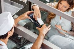 Customer Paying Through Smartphone At Butchery Stock Photography