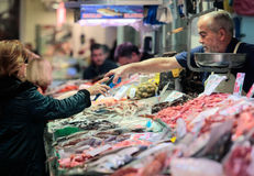 Customer paying using credit card at Fish market. A customers pays using her credit card on a stand with Fish of different species to be sold exposed on a fish stock images