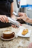 Customer Paying using NFC. Customer paying for coffee using NFC technology Stock Photos