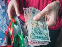 Customer pays dirhams UAE bills cash while shopping. Stock Photo