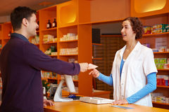 Customer in pharmacy. Giving pharmacist his prescription Royalty Free Stock Image