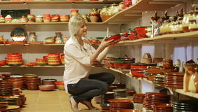 Customer picking crockery in ceramics. Cheerful female customer picking crockery in ceramics workshop stock video