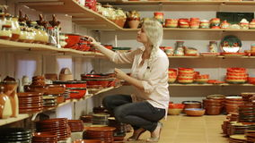 Customer picking crockery in ceramics workshop. Cheerful female customer picking crockery in ceramics workshop stock video footage