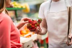 Customer picking strawberries at street market Stock Photo