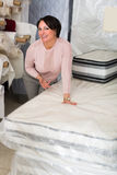Customer posing with mattress. European customer posing with mattress specimen inside textile store stock image