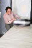 Customer posing with mattress Royalty Free Stock Image