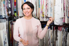 Customer posing near cloth rolls. Happy female customer posing near cloth rolls inside textile store royalty free stock photography