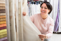 Customer posing near cloth rolls. Portrait of happy woman customer posing near cloth rolls inside textile store stock photos