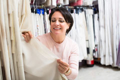 Customer posing near cloth rolls. Portrait of positive customer posing near cloth rolls inside textile store Royalty Free Stock Images