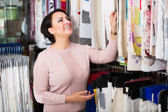 Customer posing near cloth rolls. Positive female customer posing near cloth rolls inside textile store Stock Images