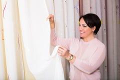 Customer posing near undercurtain fabric. Happy customer posing near undercurtain fabric inside textile store stock image
