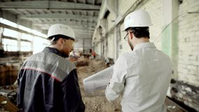The customer in a protective helmet verifies the work of builders on the object under construction, people walk through. The customer in a protective helmet on stock footage