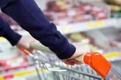 Customer pushing shopping cart. Customer pushing a shopping cart in grocery store Stock Images