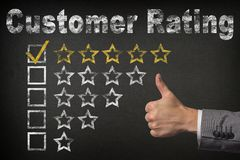 Customer Rating - 5 Five Stars with thumb up on chalkboard background royalty free stock photos