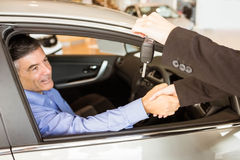 Customer receiving car keys while shaking hand Royalty Free Stock Photos