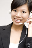 Customer Representative. Friendly Customer Representative with headset smiling during a telephone conversation Royalty Free Stock Photos