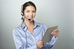 Customer Representative Holding Tablet Computer. Portrait of Smiling Young Customer Representative Woman with Headset Holding Tablet Computer While Looking at Stock Photography