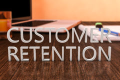 Customer Retention. Letters on wooden desk with laptop computer and a notebook. 3d render illustration Stock Photos