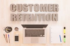 Customer Retention text concept. Customer Retention - text concept with notebook computer, smartphone, notebook and pens on wooden desktop. 3D render Stock Photos