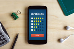 Customer review concept on smart phone screen on wooden desk Royalty Free Stock Image