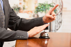 Customer ringing hotel bell at reception desk Royalty Free Stock Image