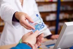 Customer's Hand Passing Money To Female Pharmacist Stock Photo