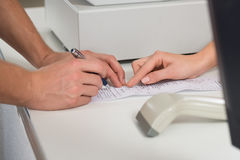 Customer's Hands Signing On Receipt At Counter In Store Stock Photography
