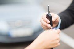 Customer and salesman with car key. Transportation and ownership concept - customer and salesman with car key outside royalty free stock photos