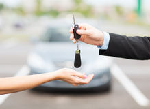 Customer and salesman with car key. Transportation and ownership concept - customer and salesman with car key outside stock images