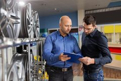 Customer and salesman at car service or auto store royalty free stock image