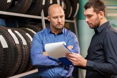 Customer and salesman at car service or auto store Stock Images